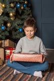 Lyckligt med ett fridsamt leende som en pojke sitter nära julgranen och betraktar en gåvaask hemma arkivfoton