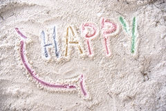 Lyckligt med ett leende som är skriftligt på en sandig strand Royaltyfria Foton