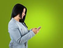 Lyckligt med hennes kommunikationer vid mobiltelefonen Arkivfoto