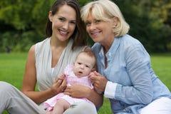 Lyckligt moder- och barnsammanträde utomhus med farmodern Royaltyfri Fotografi