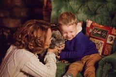 lyckligt moder- och sonsammanträde nära en julgran och en spis fotografering för bildbyråer
