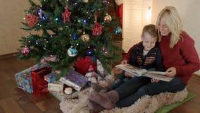 Lyckligt moder- och sonsammanträde under en julgran och bläddring av fotoalbumet lager videofilmer