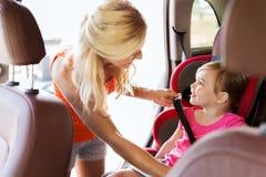 Lyckligt moderfästandebarn med bilsätebältet royaltyfri foto
