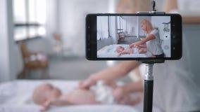 Lyckligt moderskap, bloggerförälder undervisar hur man ändrar en nyfödd flicka för blöja som ligger på ändrande tabellstundinspel arkivfilmer