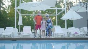 Lyckligt moget paranseende för stående på simbassängen som kramar deras lilla sondotter Farmor och arkivfilmer