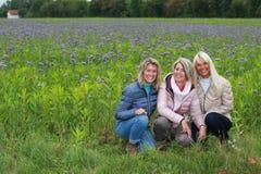 Lyckligt moget sammanträde för kvinna tre i ängen Royaltyfri Foto