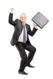 Lyckligt mogna businesspersonen med lyftt räcker och portföljen Fotografering för Bildbyråer