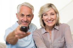 Lyckligt mogna hållande ögonen på tv för par hemma Arkivbild