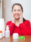 Lyckligt mogna kvinnan som gör skönhetsmedlet, maskerar på henne vänder mot Arkivbild