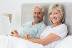 Lyckligt mogna par genom att använda den digitala minnestavlan i säng Arkivbild