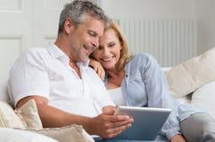 Lyckligt mogna par med minnestavlan Arkivfoton