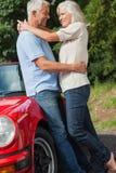 Lyckligt mogna par som kramar mot deras röda cabriolet Royaltyfria Foton