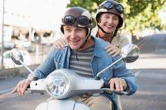 Lyckligt mogna par som rider en sparkcykel i staden Royaltyfri Fotografi