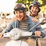 Lyckligt mogna par som rider en sparkcykel i staden Arkivfoto