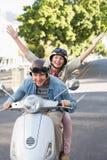 Lyckligt mogna par som rider en sparkcykel i staden Arkivfoton