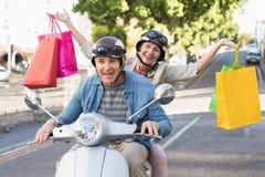 Lyckligt mogna par som rider en sparkcykel i staden Arkivbilder