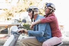 Lyckligt mogna par som rider en sparkcykel i staden Royaltyfri Bild