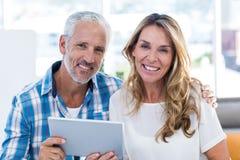 Lyckligt mogna par som rymmer den digitala minnestavlan Arkivfoton