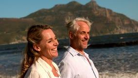 Lyckligt mogna par som tillsammans går på stranden lager videofilmer