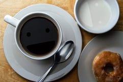 Lyckligt morgonkaffe, kräm och munk royaltyfria bilder