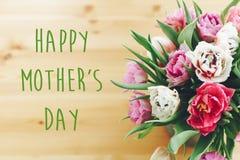 Lyckligt mors dagtexttecken på härlig dubbel piontulpanbukett i vas på trätabellen Stilfullt blom- hälsa kort än stock illustrationer