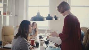 Lyckligt multietniskt möte för affärsfolk Den kvinnliga sekreteraren skriver in kontoret, ger dokument till det europeiska kvinnl arkivfilmer