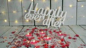 Lyckligt någonsin efter tecken med röda hjärtor omkring och stearinljus som tänds upp Ljus på backround red steg