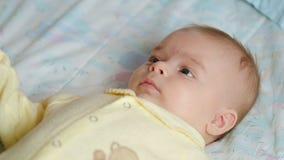 Lyckligt nyfött behandla som ett barn att ligga på sängen arkivfilmer