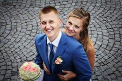 Lyckligt nyligen gift par som ler ståendenärbildsikt från a Royaltyfri Foto