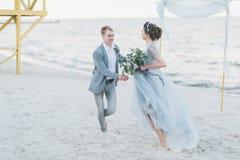 Lyckligt nyligen-gifta sig har gyckel och spring vid havet Arkivfoton