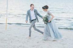 Lyckligt nyligen-gifta sig har gyckel och spring vid havet Royaltyfria Foton