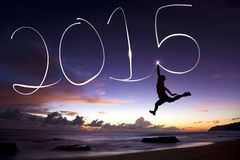 Lyckligt nytt år 2015 banhoppning och teckning 2015 för ung man arkivfoto