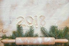 Lyckligt nytt år 2018 för tecken i mjölet på trätabellen som dekoreras med jul tre filialer och pudrad rullande pi Royaltyfri Foto