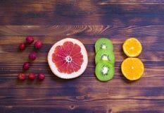 Lyckligt nytt år 2018 gjorde av frukt och bär på träbakgrund Arkivfoto