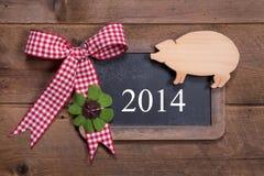 Lyckligt nytt år 2014 - hälsningkort på en träbakgrund med Arkivfoton