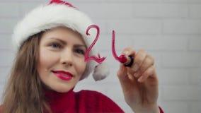 Lyckligt nytt år 2018 Jultomtenflickan skriver på glass ord 2018 med läppstift Härlig flicka i jultomtenhatten som överför ett me stock video