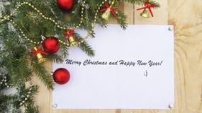 Lyckligt nytt år och glad jul på papper, bakgrundsbräde, julgranen och garneringar Arkivbild