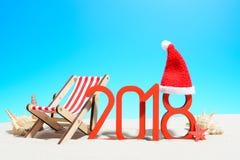 Lyckligt nytt år på strandbegreppet tecken 2018 och en vardagsrumstol med en jultomtenhatt Royaltyfri Bild