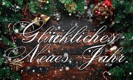 Lyckligt nytt år som visas på en lantlig trätabell med garnering, gåvor, snö, trädfilial i tysk fotografering för bildbyråer