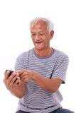 Lyckligt och att le, kopplad av gammal hög man som använder smartphonen Royaltyfri Fotografi