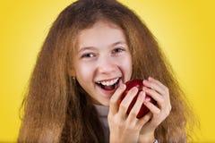 Lyckligt och att le lilla flickan som rymmer ett rött äpple som äter det isola arkivbild
