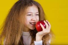 Lyckligt och att le lilla flickan som rymmer ett rött äpple som äter det isola royaltyfri foto