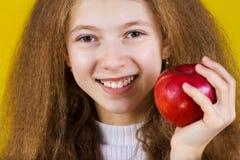 Lyckligt och att le lilla flickan som rymmer ett rött äpple som äter det isola royaltyfria foton
