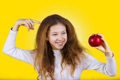 Lyckligt och att le lilla flickan som rymmer ett rött äpple som pekar med f fotografering för bildbyråer