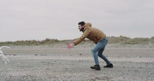 Lyckligt och le att spela för man som är roligt med hans dalmatian hund på stranden Bra seende hund som kör med en boll på hans arkivfilmer