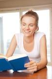 Lyckligt och le den tonårs- flickan med boken Fotografering för Bildbyråer