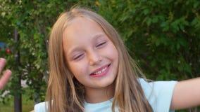 Lyckligt och le tonåringflickan som spelar med hennes utomhus- blonda hår stock video