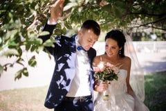 Lyckligt och ungt gift par som går med en bukett av blommor arkivfoto