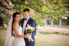 Lyckligt och ungt gift paranseende under trädet med en bukett av blommor royaltyfri fotografi