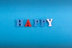 LYCKLIGT ord på blå bakgrund som komponeras från träbokstäver för färgrikt abc-alfabetkvarter, kopieringsutrymme för annonstext l Fotografering för Bildbyråer